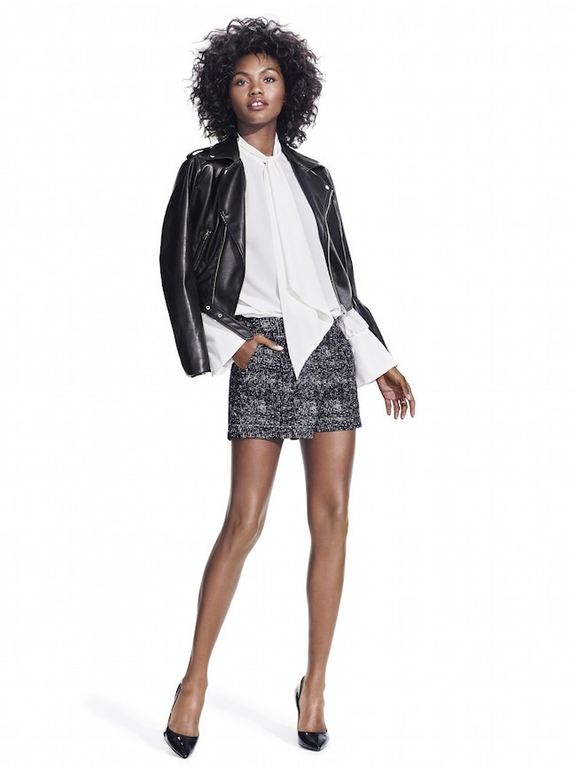 Studio-Model-wearing-black-leather-jacket-over-white-neck-tie-blouse-with-bacl-and-white-shorts-with-black-pointed-pumps