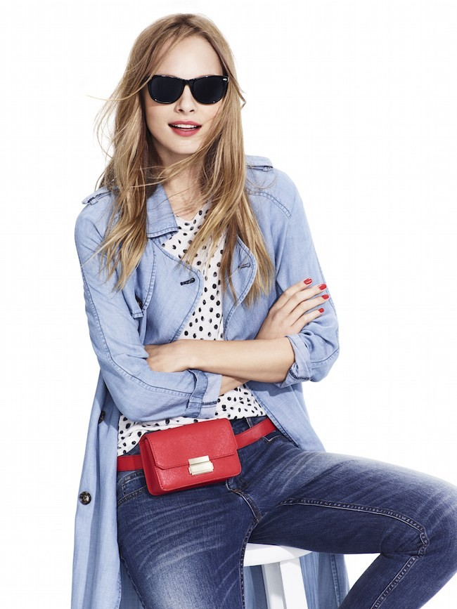 Studio-Model-wearing-light-blue-coat-with-black-and-white-dot-tee-shirt-red-leather-fanny-pack-dark-jeans-and-sunglasses